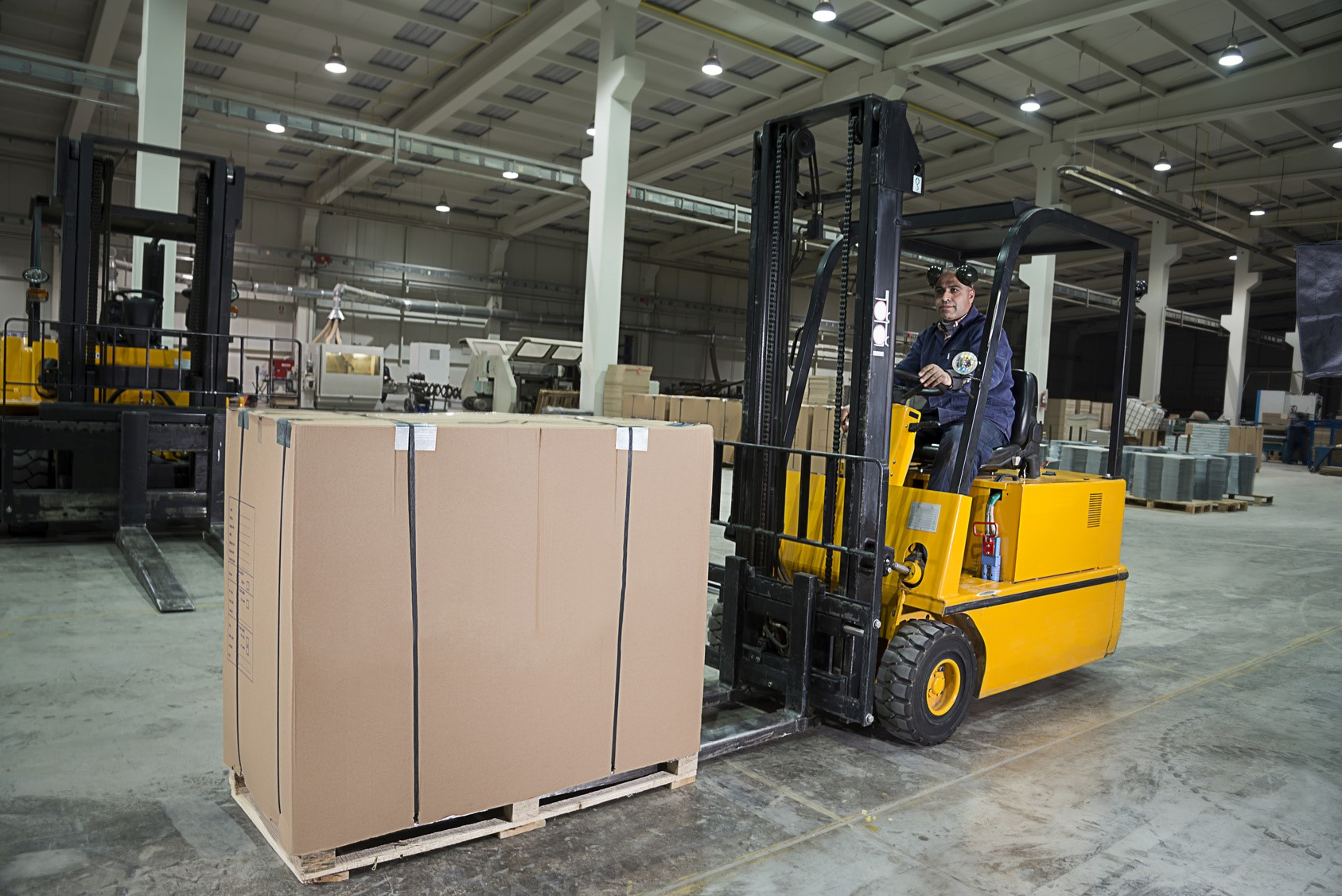 forklift hauling brown box